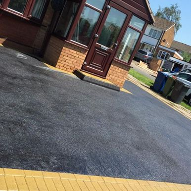 brown front door with black tarmac driveway